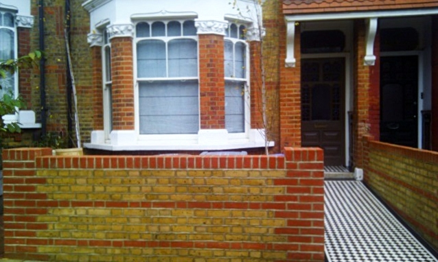London brick wall and Victorian black and white mosaic tile path