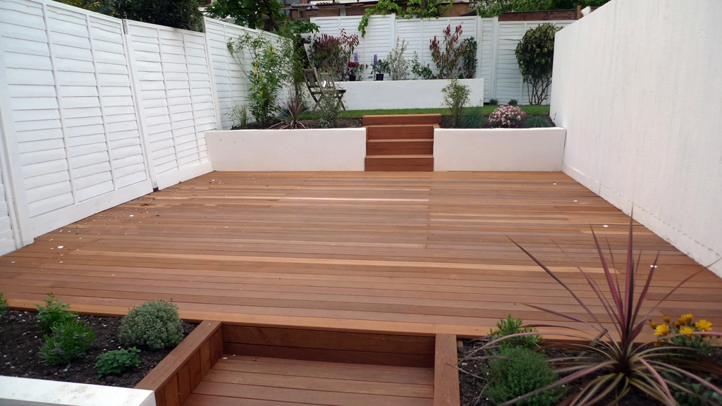 hardwood decking rendered smooth walls white fence and modern planting garden design london