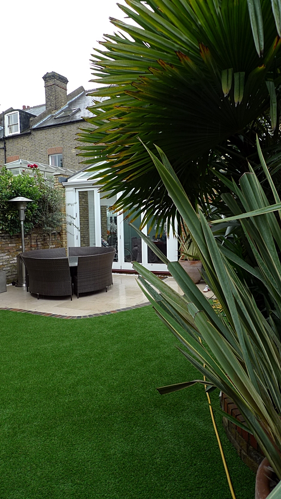 new limestone patio paving tile slabs with easy lawn grass in walled garden london