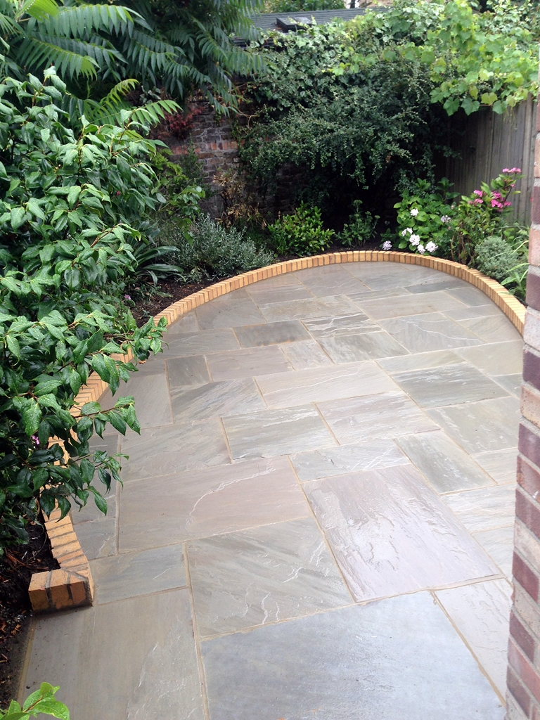 sandstone paving patio set on rounded curve with small brick wall London