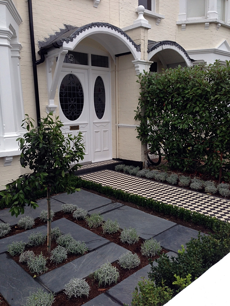 classic victorian front garden with formal topiary mosaic and slate paving