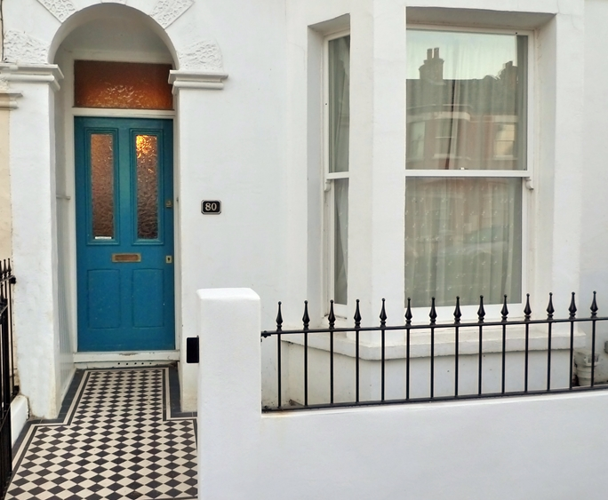 black and white mosaic tile path with white painted wall with meatl rail and cast iron gate london
