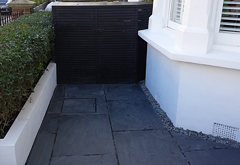 slate paving and black slatted bin store