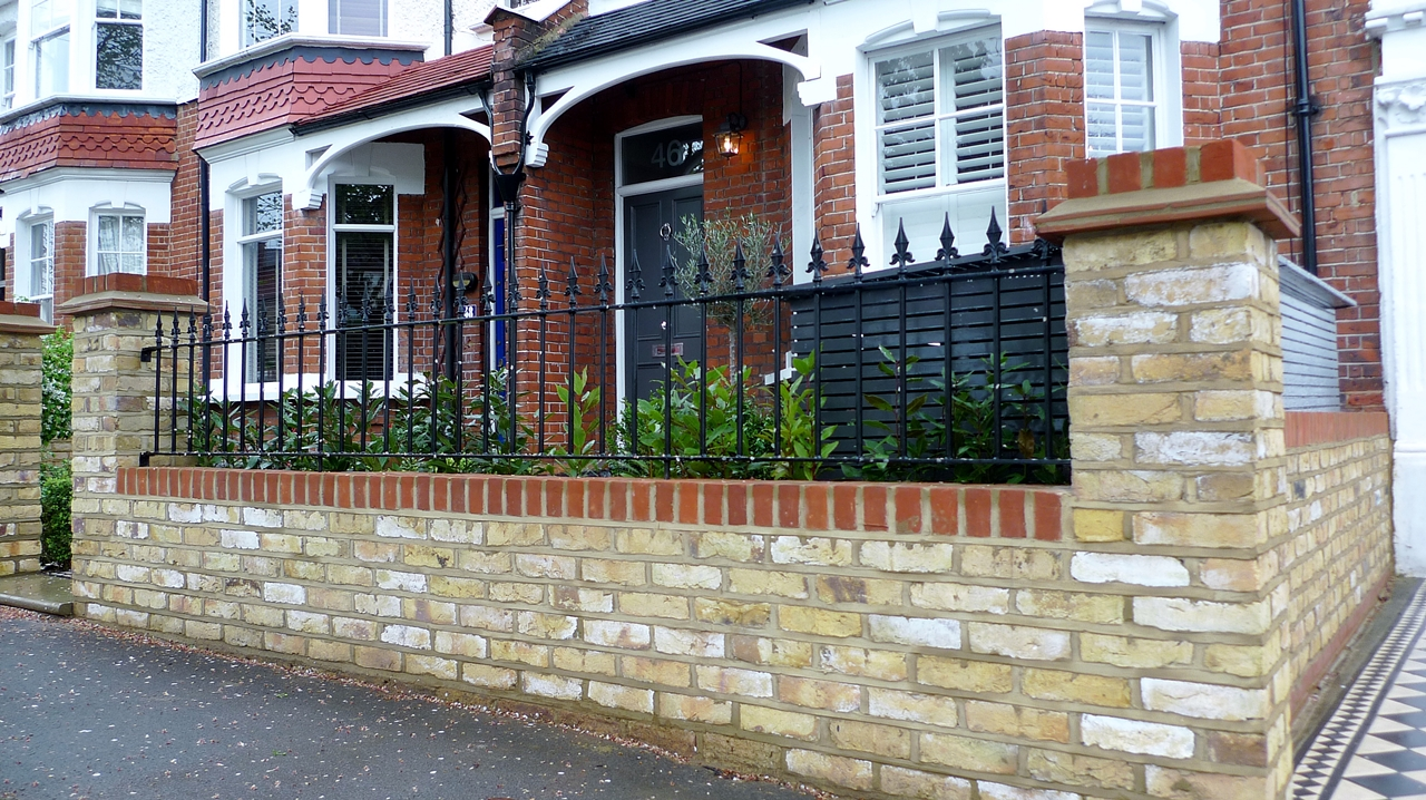 London yellow stock brick wall with red rubber brick trim and metal spear rail