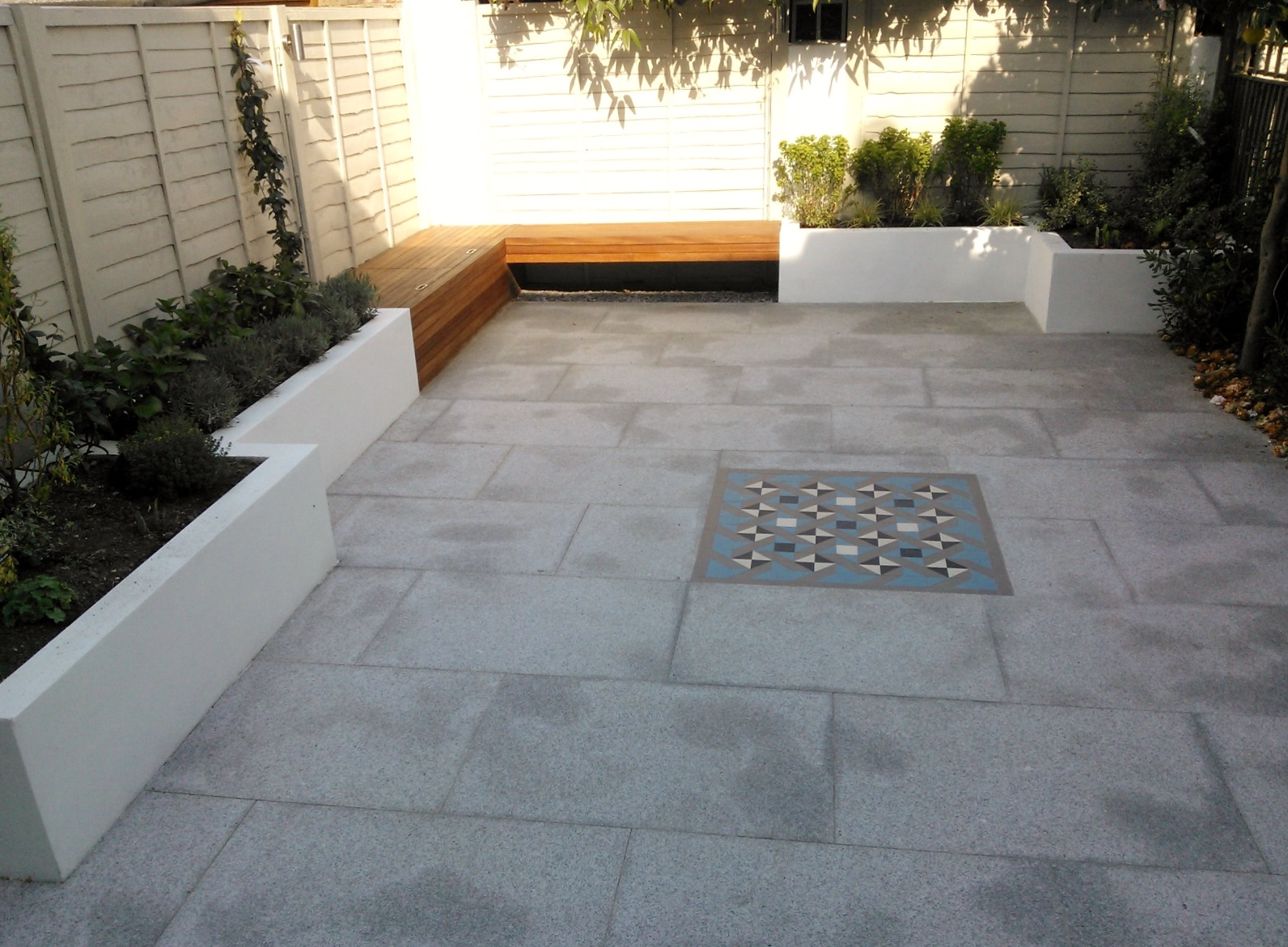 Modern London Garden Design Painted Fence Granite Paving Hardwood Bench Raised Painted beds architectural Planting West London (4)