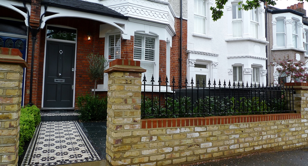 New yellow stock garden wall London with metal wrought iron steel rail and victorian mosaic tile path