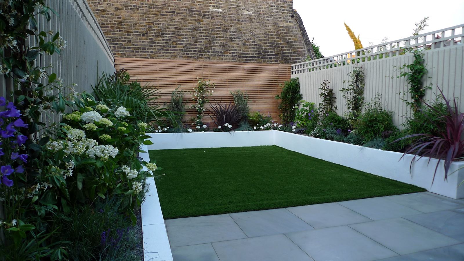 sawn grey sandstone paving raised rendered beds hardwood screen painted stone fence london small garden design (1)