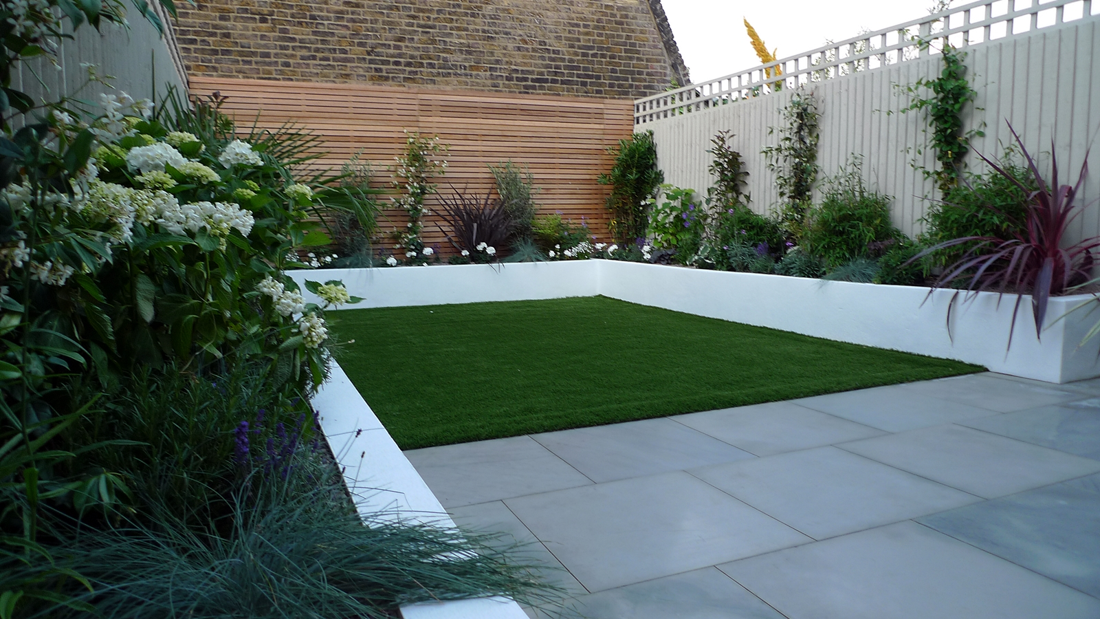 Sawn grey sandstone paving raised rendered beds hardwood for Little garden design