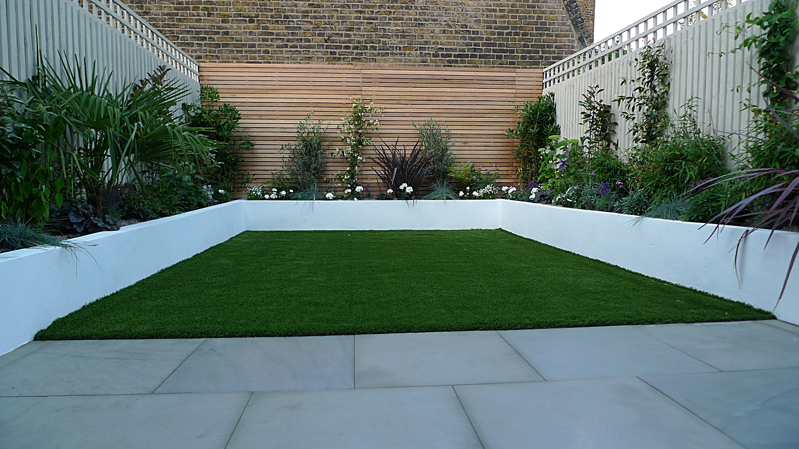 sawn grey sandstone paving raised rendered beds hardwood screen painted stone fence london small garden design (7)