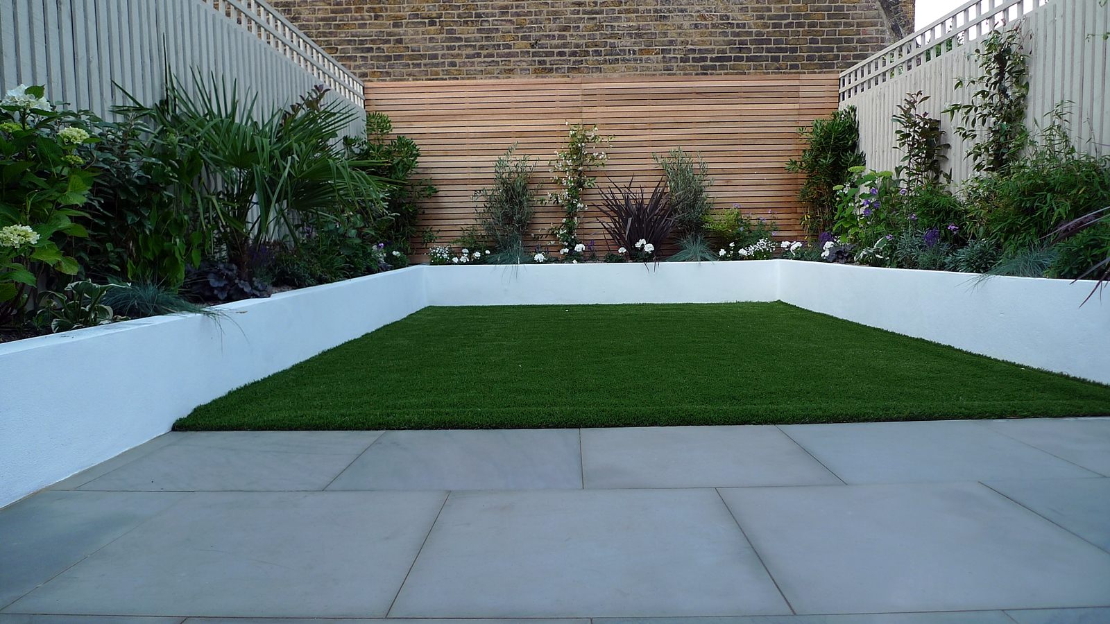 sawn grey sandstone paving raised rendered beds hardwood screen painted stone fence london small garden design (8)