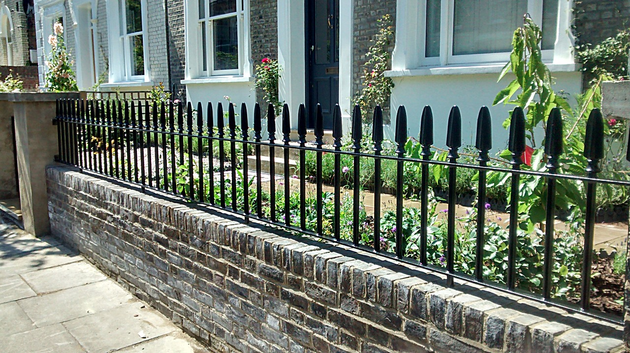 front garden yellow brick wall and wrought iron metal rails and gate islington london