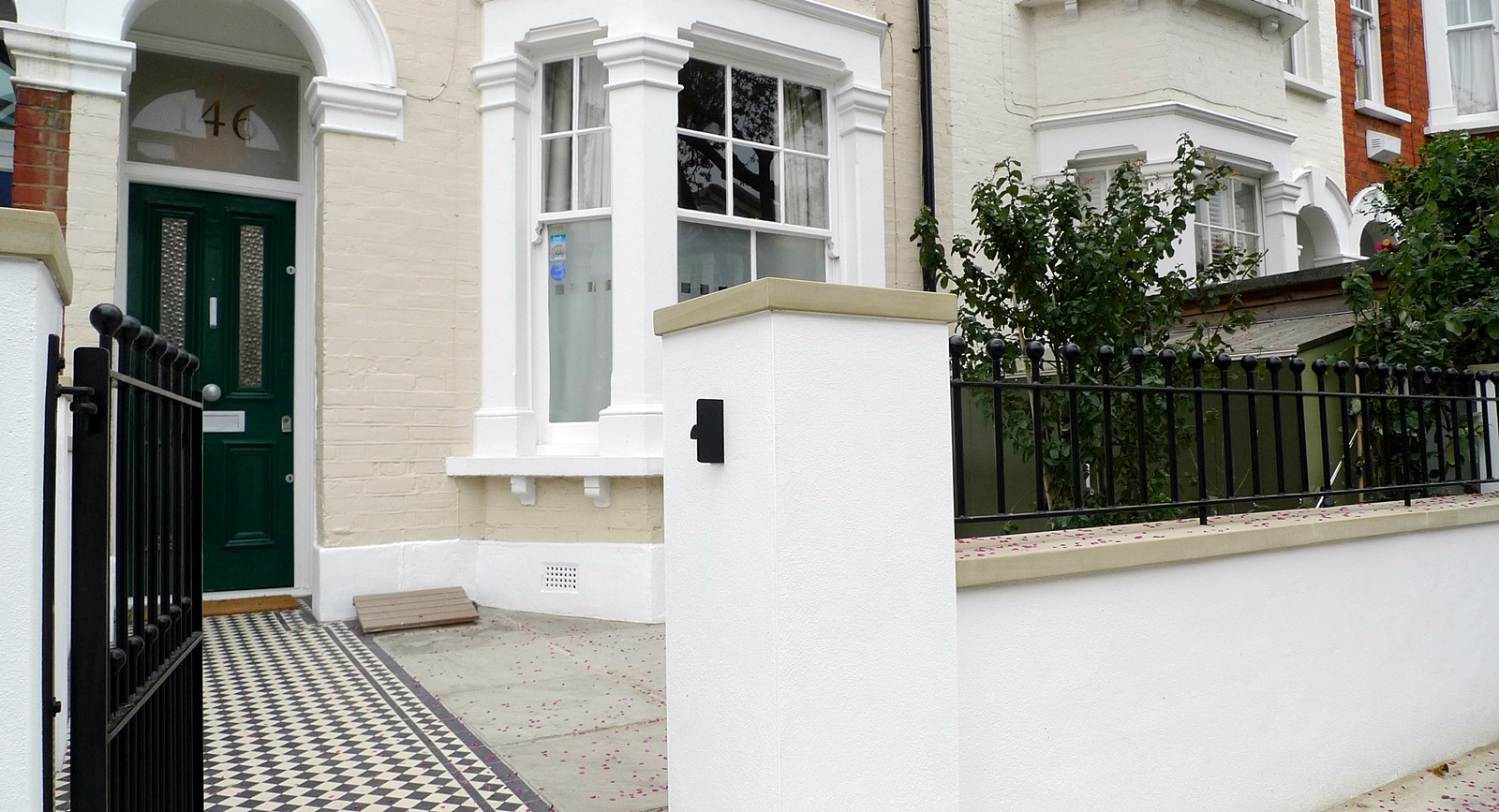 render plaster block wall with yorkstone caps wrought iron rail grey sandstone paving and black and white victorian mosaic tile path balham london (3)