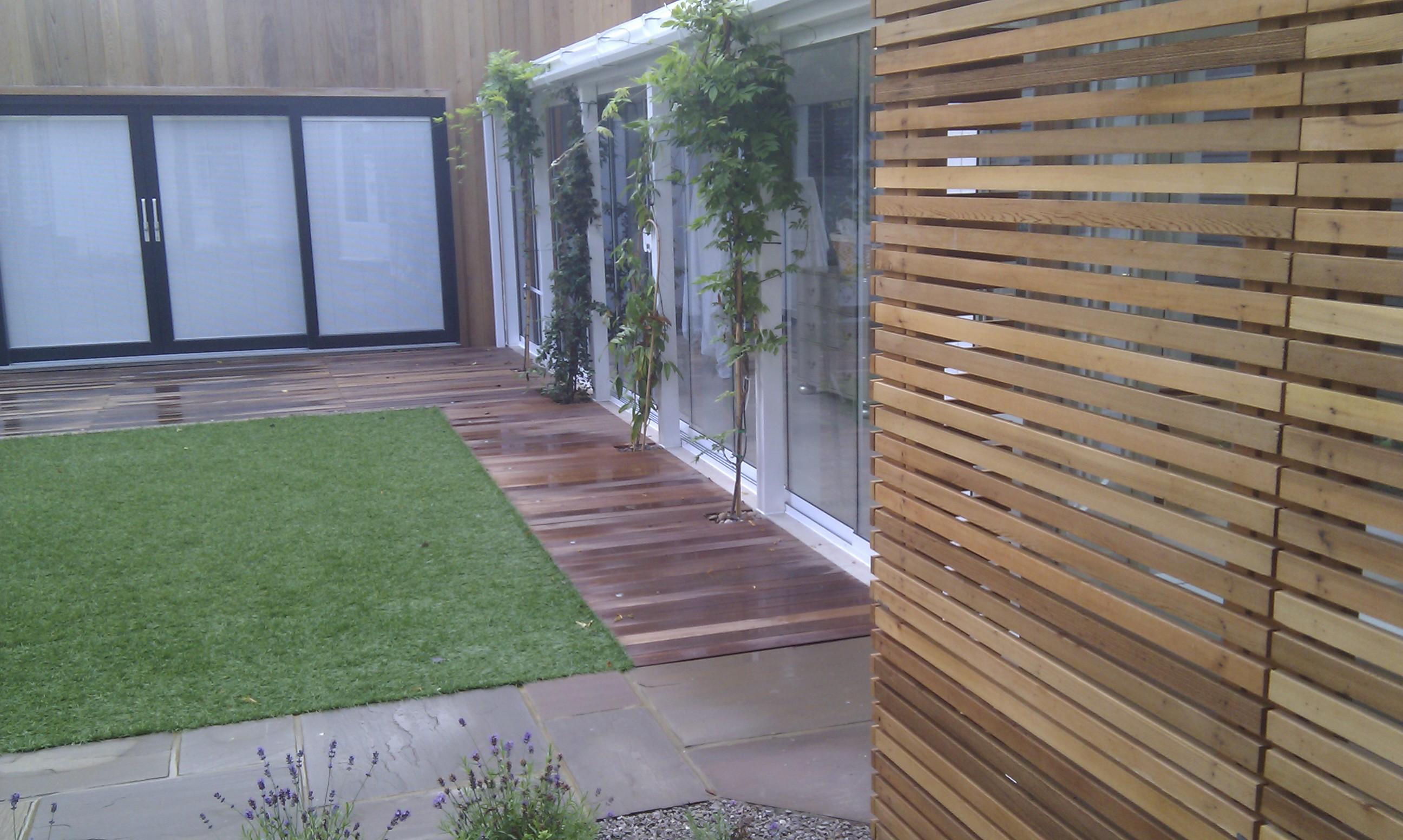 modern garden design london slatted grey privacy screen sandstone paving easy grass balau hardwood decking (24)