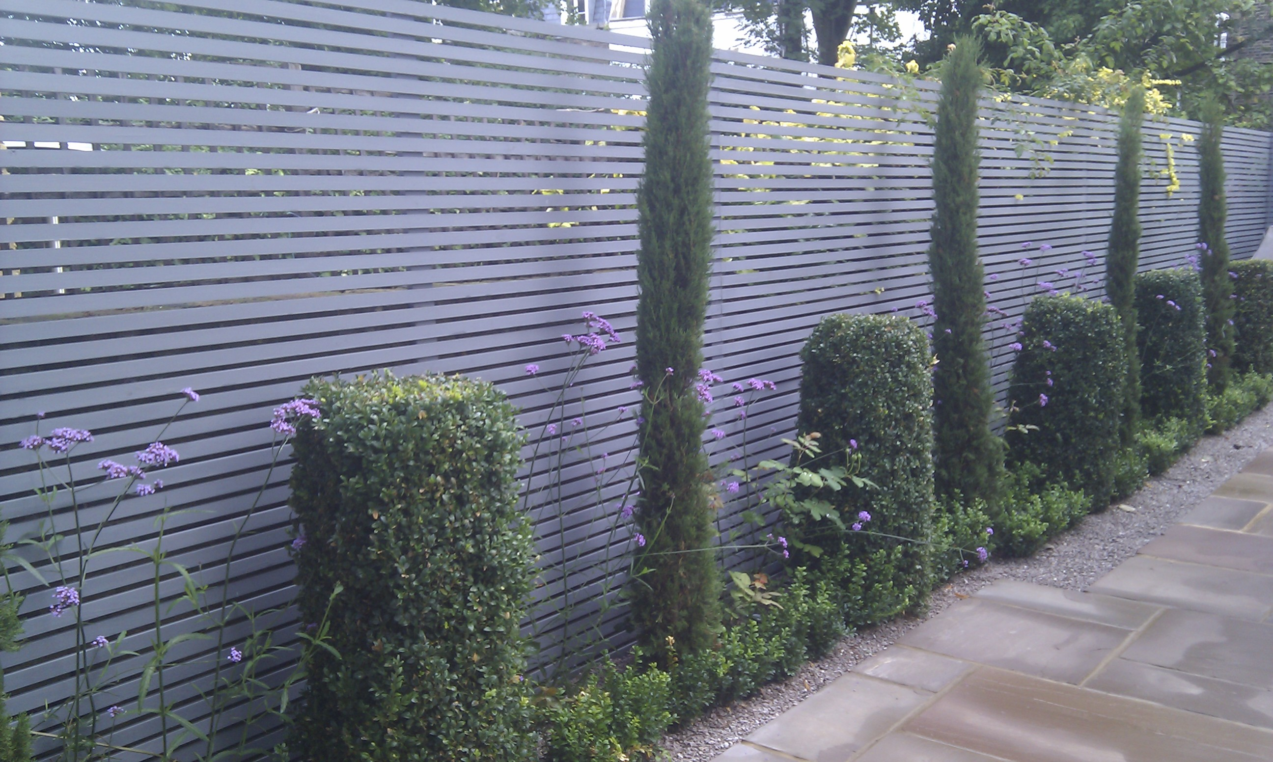 Modern garden design london slatted grey privacy screen for Garden decking and grass