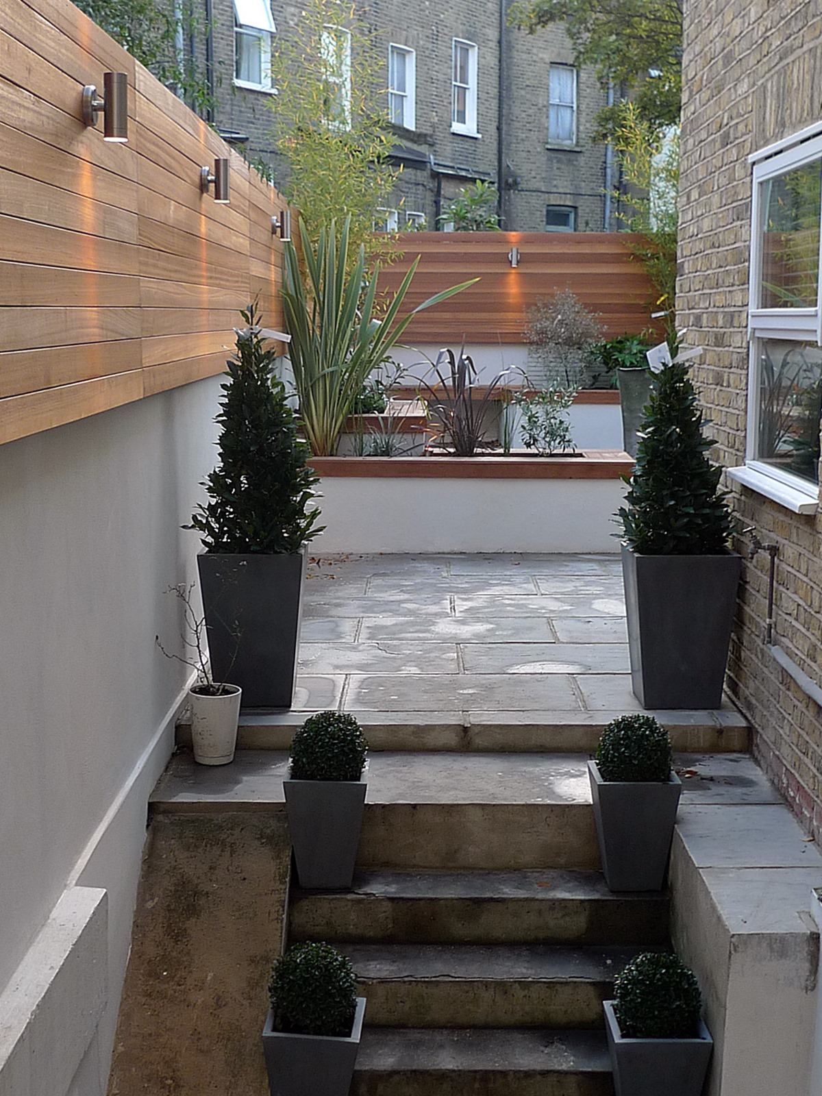 modern london courtyard low maintenance urban outdoor indoor living garden space paving screens planting bench raised beds (2)