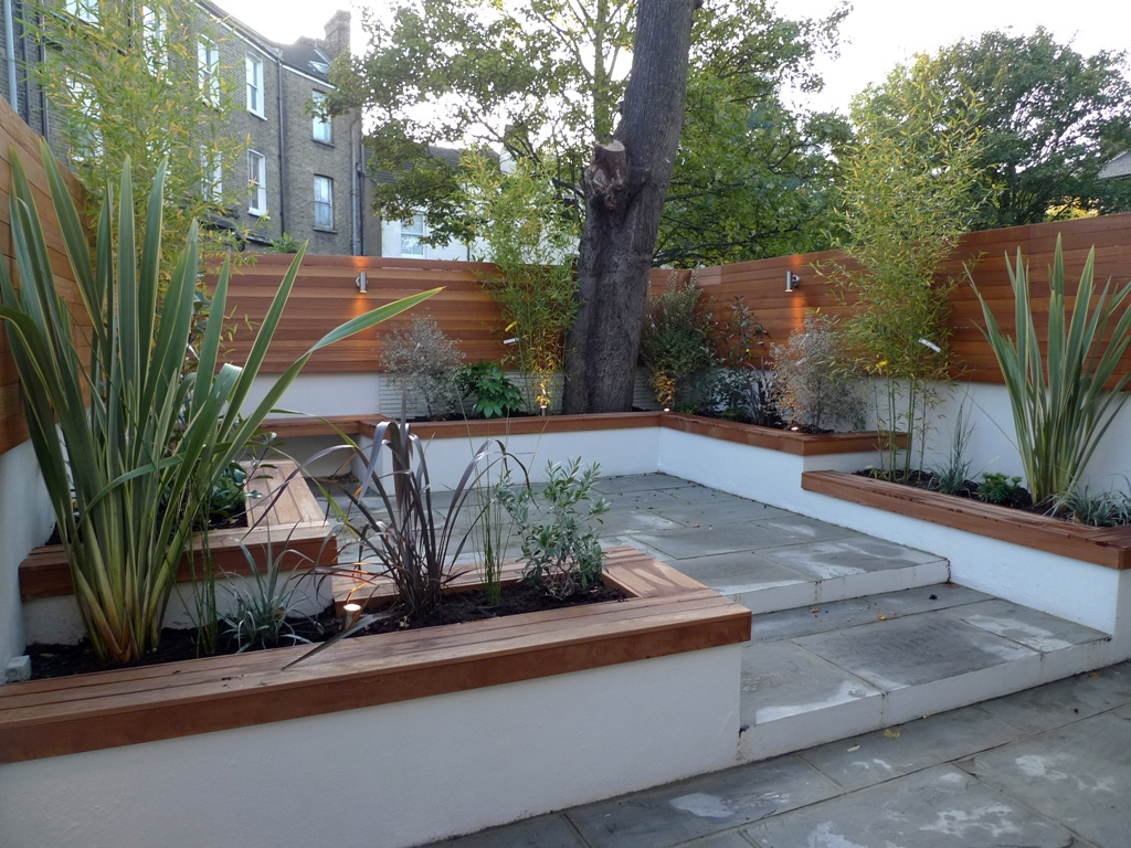 modern london courtyard low maintenance urban outdoor indoor living garden space paving screens planting bench raised beds
