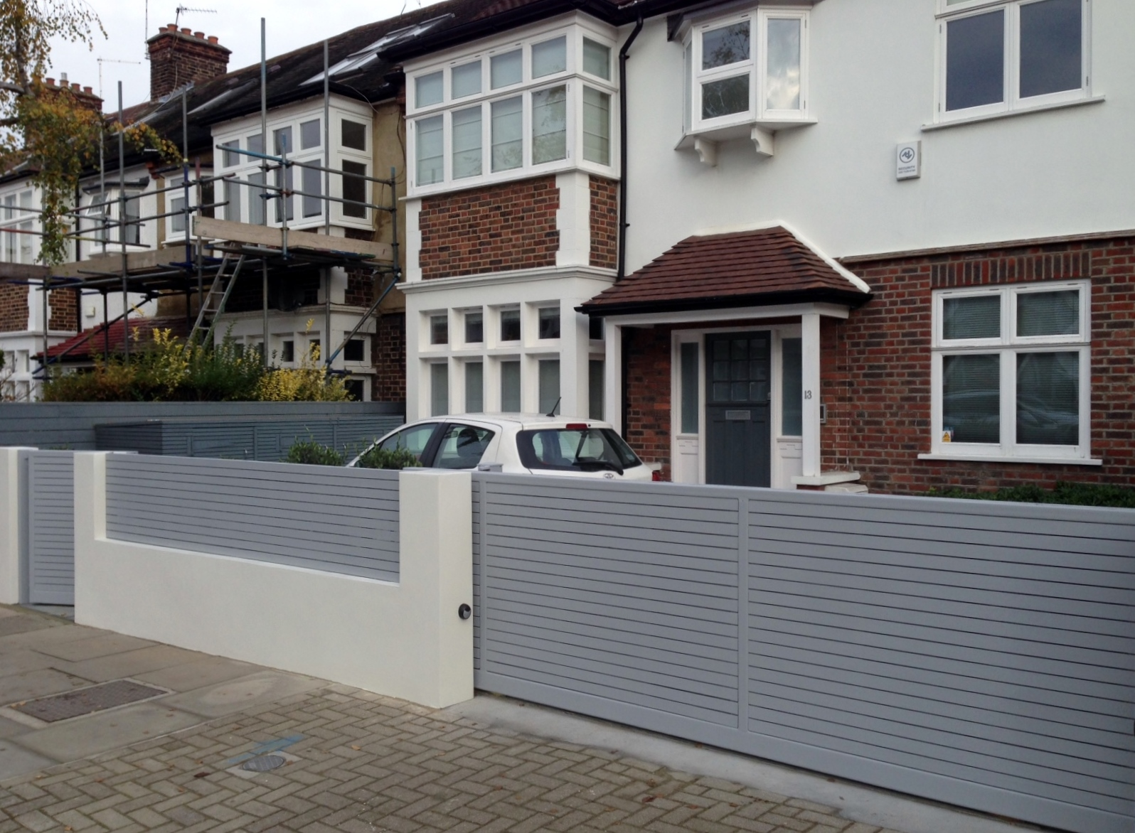 Front boundary wall screen automated electronic gate installation grey wooden fence bike store modern garden design balham clapham london