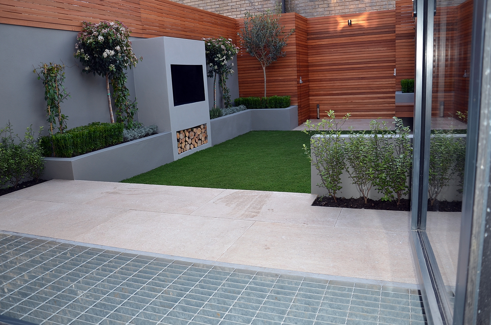 beige limestone paving fake artificial grass lawn outdoor fire place BBQ floating bench hardwood slatted privacy screen and doors bespoke storgae unit London