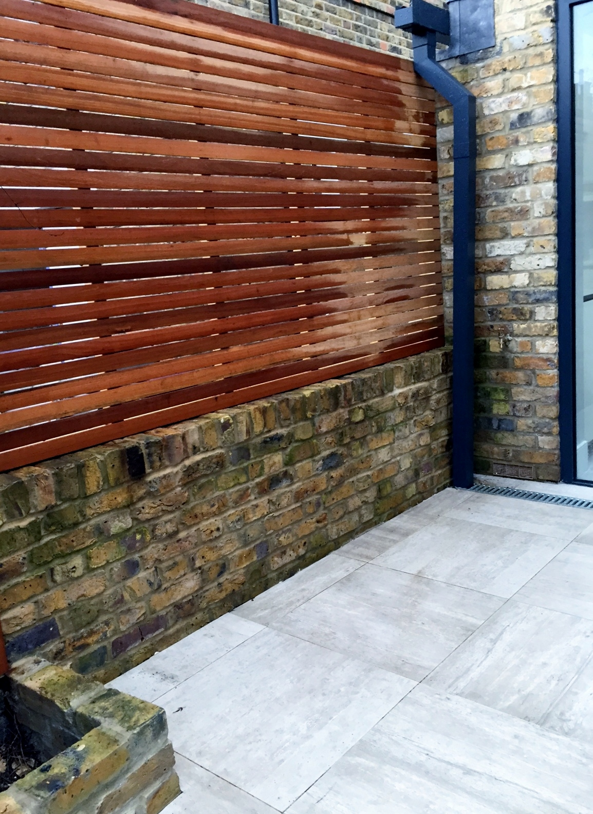 hardwood screen and patio paving cream tile stock brick wall london