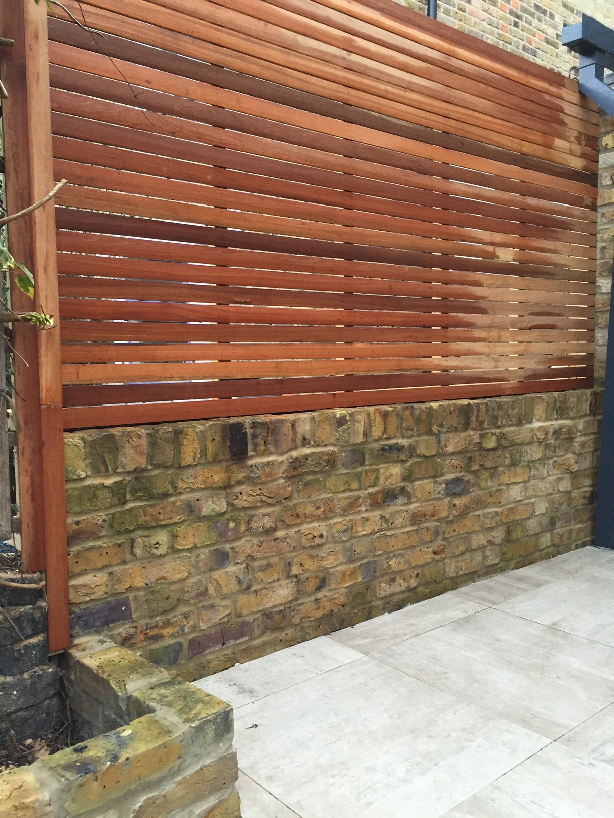 Hardwood screen trellis on yellow stock brick wall london for Designs for brick garden walls