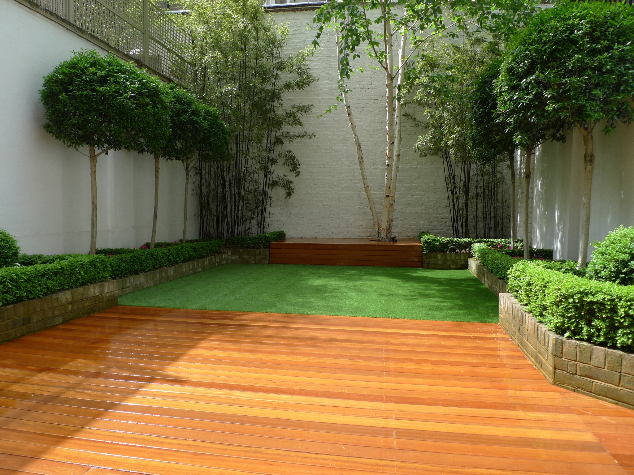 Chelsea garden design hardwood decking artificial grass for Modern garden decking designs