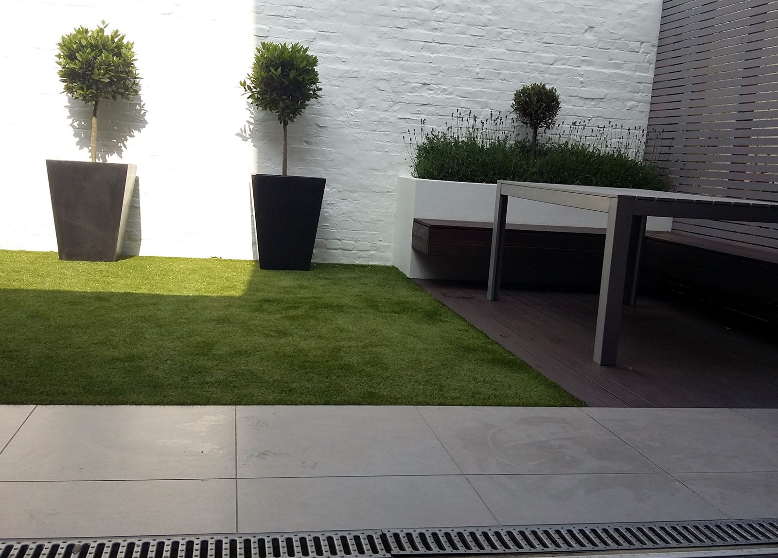 modern courtyard garden design putney and wandsworth london fake grass hardwood decking raised painted beds slatted grey privacy screen trellis