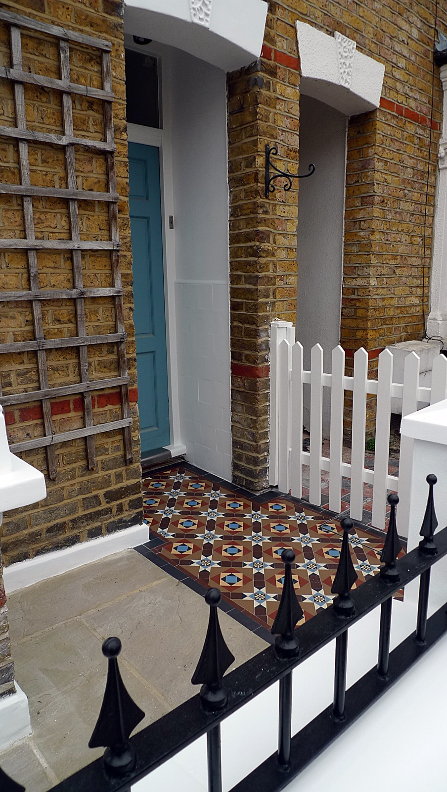 new garden wall painted white metal rail painted black sandstone paving colourful victorian mosaic tile path london front garden company