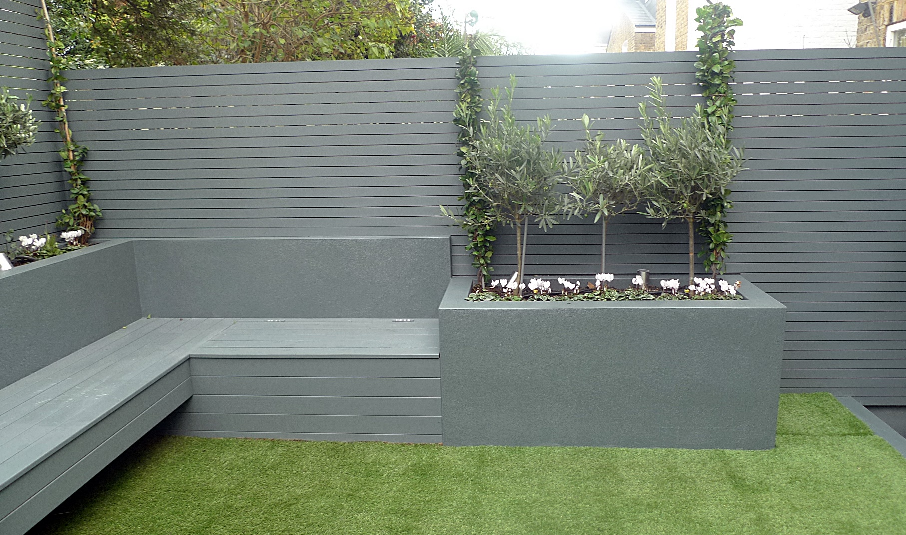 Grey colour scheme artificial grass raised beds porcelain grey tiles grey Floating bench agapanthus olives yellow stock brick wall Clapham Balham Wandsworth Battersea Fulham Chelsea London