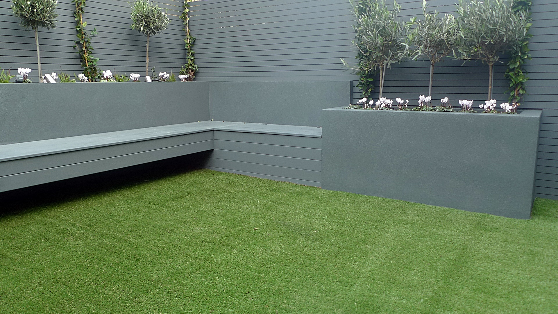 Grey colour scheme raised beds artificial grass olives agapanthus porcelain grey tiles grey Floating bench lighting Balham Wandsworth Clapham Battersea Vauxhall Fulham Chelsea London