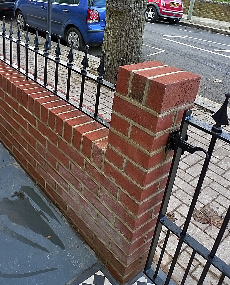 Brick garden red wall iron rail metal gate privacy formal bespoke London Chelsea Fulham Battersea