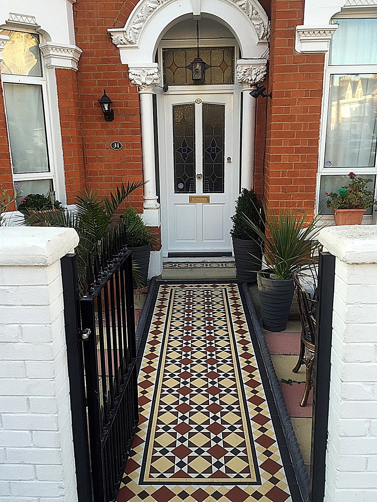 Metal gate rails white brick wall painting multi colour mosaic front garden company iron tile path London Wandsworth Balham Clapham