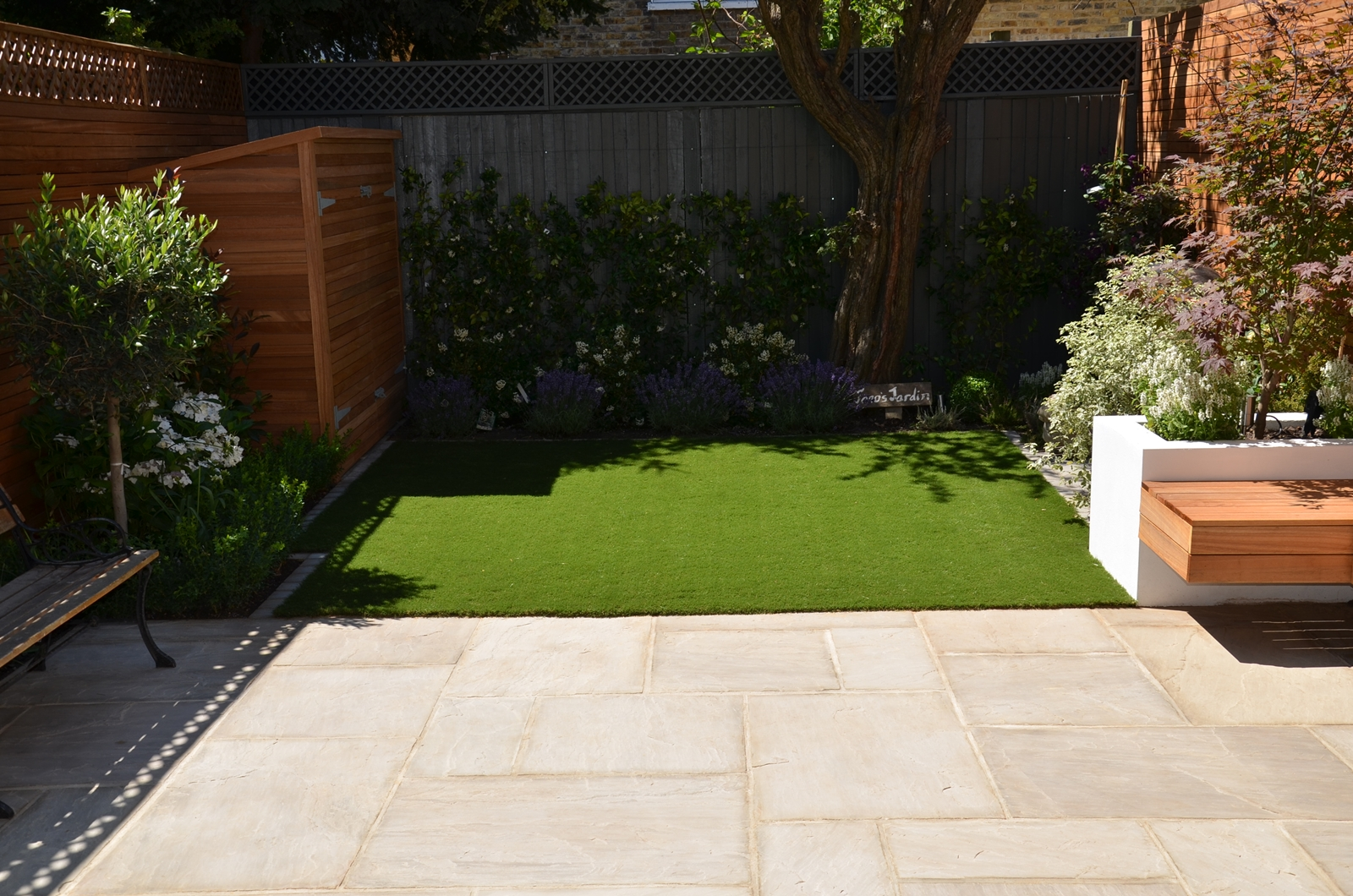 sandstone paving hardwood screen bespoke shed flaoting bench rich layered planting garden design london